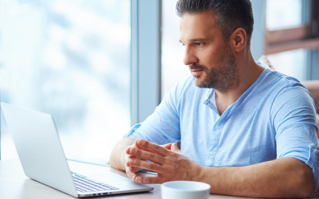 Adulto negociando online para comprar imóvel no Brasil morando no exterior.