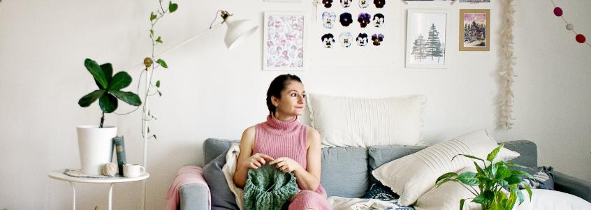 Jovem sentada no sofá da sua casa fazendo tricô.